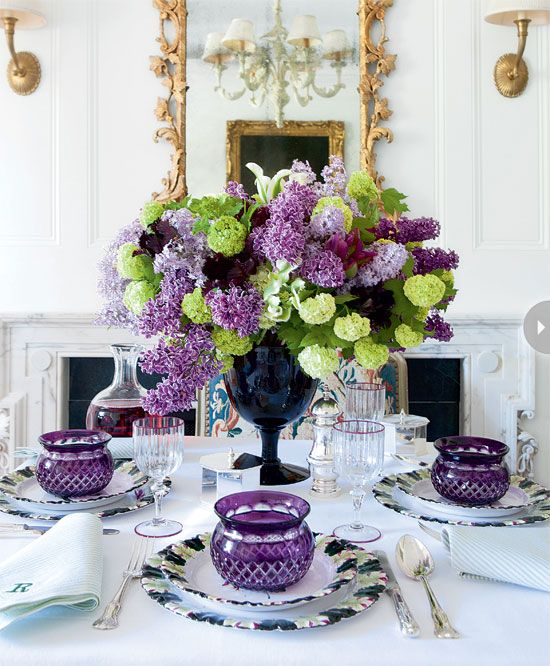 """Carolyne Roehm employed a variety of textures in a simple palette spilling out of a wide-mouthed vase. """"Lilacs and viburnum make good companions – each is a thousand flowers in one,"""" she explains."""