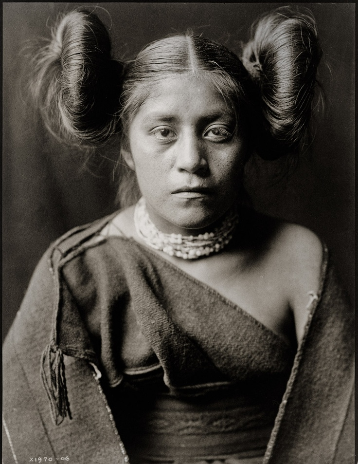 """A Tewa Girl photographed by Edward Curtis in 1906. Half-length portrait, facing front, hair arranged in """"squash blossom"""" fashion."""