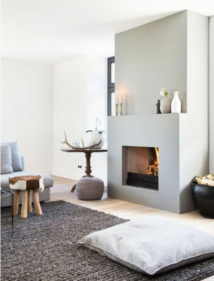 tapis gris scandinave dans le salon avec murs beiges et cheminée d'interieur