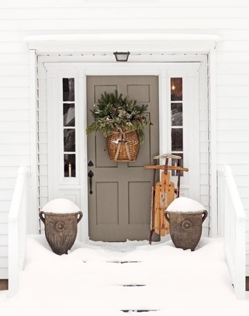 Winter decor - Taupe door, white trim, basket with greenery and bow on door, sled propped against house, snow filled urns flanking the door