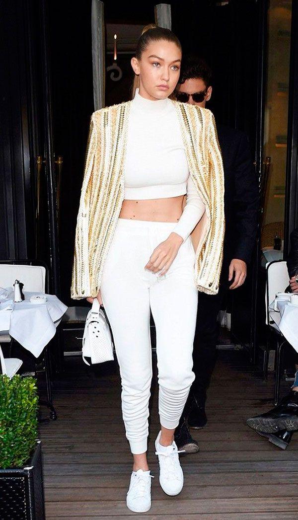 Street style look Gigi Hadidi calça, cropped e tenis branco com jaqueta dourada.