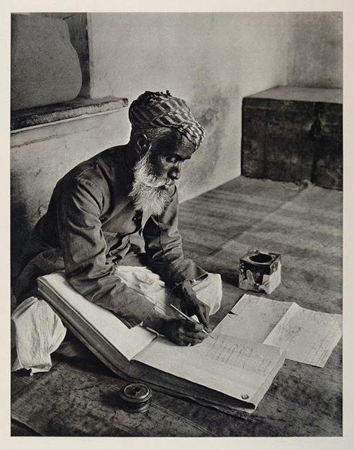 Indian street banker making notes in Urdu in a ledger book, Udaipur, 1928