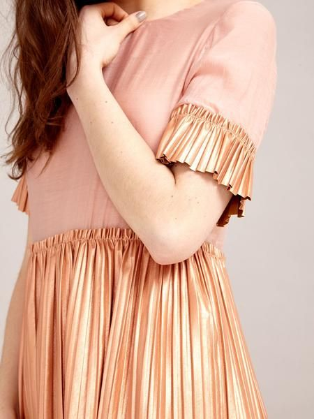 Blush top with a sheer bodice and contrast copper pleated sleeves and peplum. Please be aware that this garment is delicate and can be damaged by rough handl...