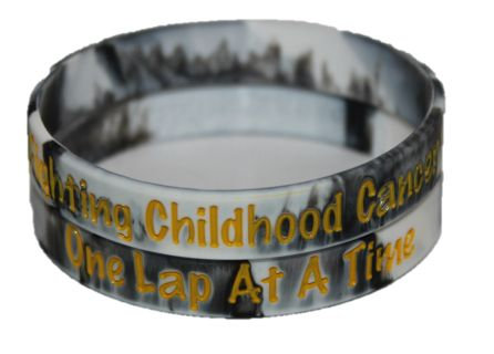 """Show your support for families fighting Childhood Cancer with this Racing 2 Cure wristband. Featuring black and white checkered swirl and writing in Childhood Cancer gold. This wristband comes in two sizes Adult and Youth.  The outside of the wristband reads """"Fighting Childhood Cancer One Lap at a Time,"""" while the inside has the Racing 2 Cure website. 100% of the proceeds from the purchase of this wristband directly benefits families dealing with cancer. Each wristband was also made in the…"""