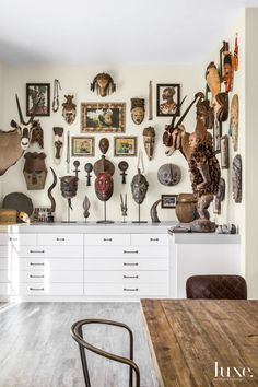 Tribal masks and artwork from the homeowners' collection are hung en masse above streamlined custom drawers built by Tharp Cabinet Company in the studio. The flooring is from Bedrosians Tile & Stone.