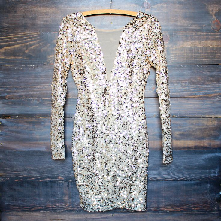 An amazing gold sequin dress that features long sleeves, a mesh front v panel, a deep v back neckline, and a hidden zipper with hook closure. This perfect numbe