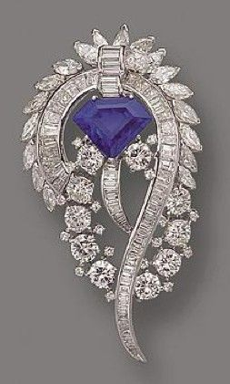 SAPPHIRE AND DIAMOND BROOCH. The stylized foliate scroll set in the center with a shield-shaped sapphire weighing 5.90 carats, completed by 19 marquise-shaped, 61 baguette and 27 round diamonds weighing approximately 9.25 carats, mounted in platinum.