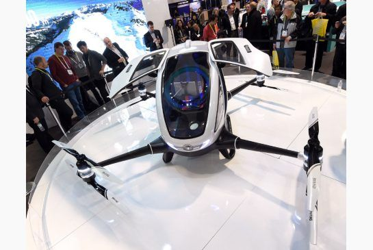 Attendees look at an EHang 184 autonomous-flight drone that can fly a person at CES 2016 at the Las Vegas Convention Center on Thursday in Las Vegas. The 18-foot-long, 440-pound drone has four arms and can carry one passenger who does not need to pilot the drone.