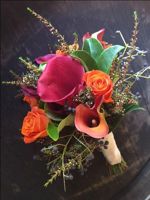Calla lilies in orange , burgundy, roses and thrift @weddingflowersetc