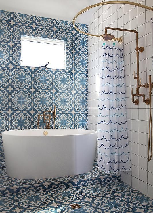 Exquisite Mediterranean themed bathroom is clad in Cement Tile Shop Bordeaux Tiles that cover the floor and an accent wall fitted with a window positioned above an oval freestanding bathtub with a floor mount tub filler.