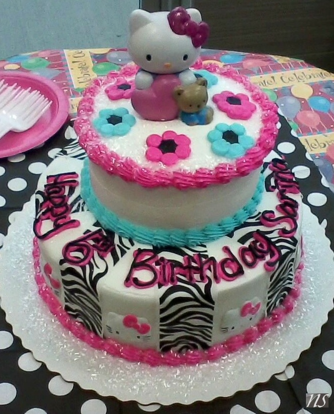 Shekinah likes the flowers, the pink and blue colors, and the zebra things being ribbons instead. And the sugar glitter. Hello Kitty Blue and Pink Zebra Cake, Buttercream - Nikki Stine