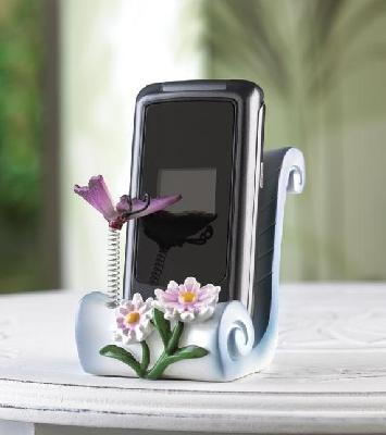 """Butterfly Cell Phone Holder  No more hunting for that cell phone; this decorative cradle holds it oh-so-prettily in place! An enchanting accessory wherever it's placed, with a whimsical bouncy butterfly and flower theme.     Weight 0.2 lb. Polyresin. Cell phone not included. 2 3/8"""" x 2 1/2"""" x 3"""" high."""