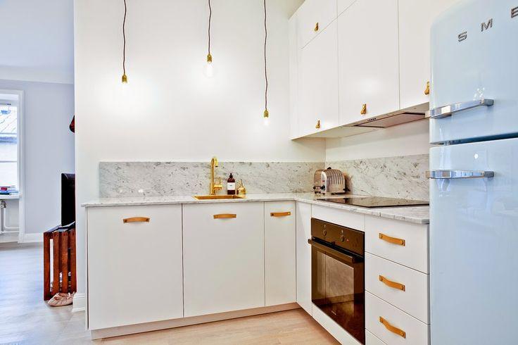 Białe szafki i złote dodatki do kuchni