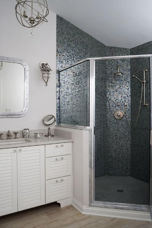 Amazing bathroom features a white beadboard vanity adorned with glass knobs paired with a gray countertop under a Restoration Hardware Submarine Inset Medicine Cabinet illuminated by nautical sconces and a nickel sphere chandelier.
