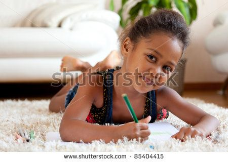 Little African Asian girl  drawing, lying down on the floor - stock photo