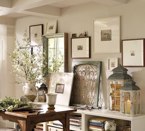 Several items in this photo:  1. the framed metal fencing, antiqued  2. stack of old books inside the vintage candle lamps  3. the mirror in the oversized frame (ask James to make for me)