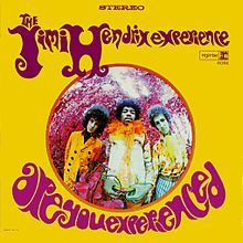 A color image of three men standing together wearing psychedelic clothing.