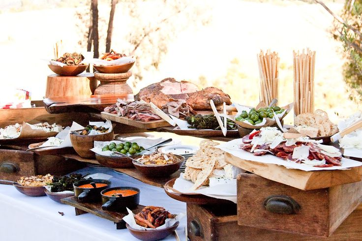 A rustic canapé table with wooden boards of charcuterie and bowls of olives