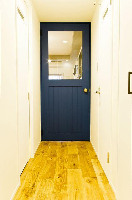 京都府京都市の築12年の中古マンションをリノベーション。リビングは部分的な躯体現しで空間にメリハリをつけています。子供部屋は閉鎖的にならないように、リビングとの繋がりを意識できる回転窓を設けました。さらに今回は、廊下とリビングを繋ぐ紺色の建具が空間のアクセントとなっています。