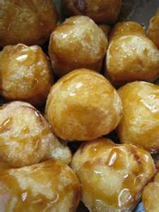 Cascaron a filipino dessert made out of sweet rice flour mixed w/ sugar, rolled into balls, deep fried, then melted brown sugar drizzled on top.  I'm hungry!