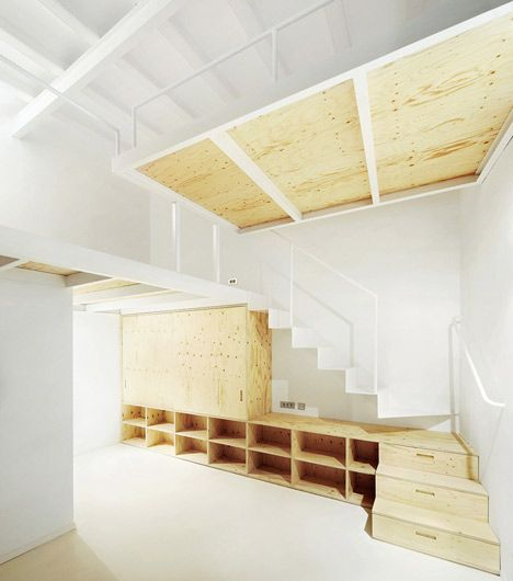 A renovated apartment in the El Born area of Barcelona featuring wooden storage and mezzanines.