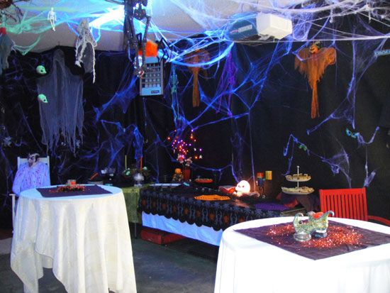 Winn transforms her garage with black tarps, spiderwebs, black lights, hanging skeletons and ghouls.