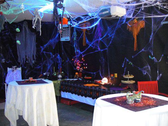 Winn transforms her garage with black tarps, spiderwebs, black lights, hanging skeletons and ghouls.