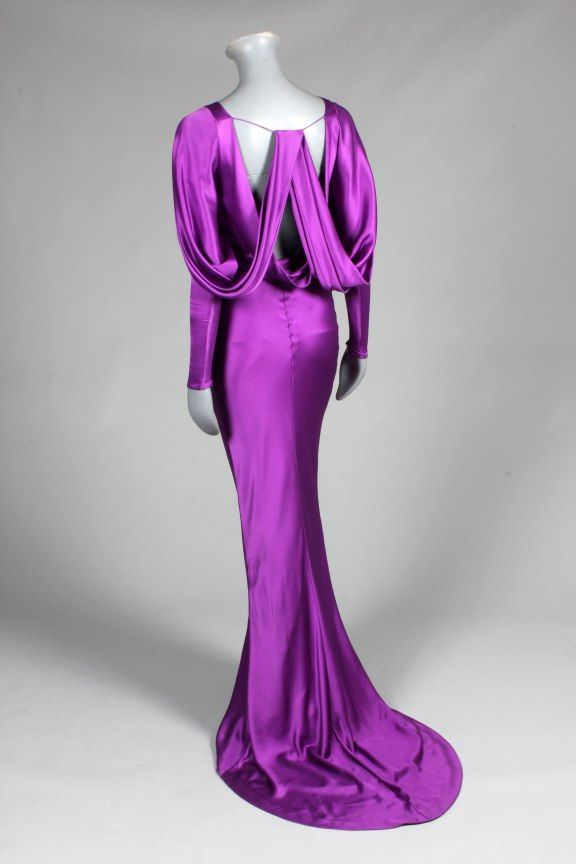 * An Alexander McQueen purple satin evening gown, with cowl neck, draped dolman sleeves with narrow zippered cuffs, bias cut skirt with fish-tail hem, spaghetti strap to the low back opening which catches the draped swags which fall from the shoulders