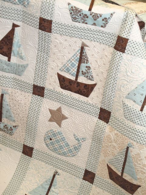 I like the quilting design of this.  around the boats and whales are swirls designs, while the piecing is several rows of straight line stitching,  gives a really nice effect.