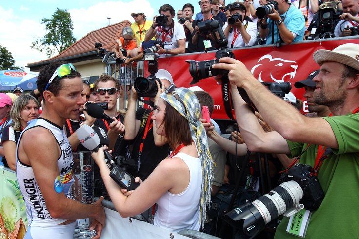 The world's fastest iron distance triathlete, Andreas Raelert gets mobbed by media after breaking the world record at Challenge Roth 2011.