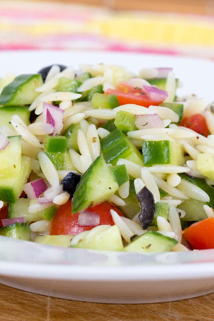 Greek Orzo Pasta Salad Recipe with tomato, cucumber, red onion, artichoke hearts, feta cheese, and black olives in a red wine vinegar dressing