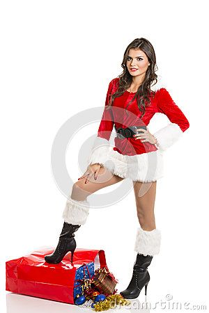 Smiling sexy girl dressed in Santa Claus clothes posing with one leg on big red bag full of Christmas presents.