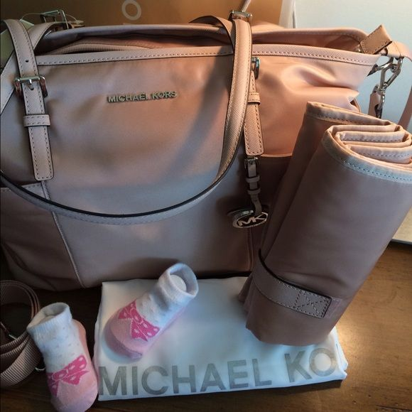 """Diaper BABY BAG Jet Set Michael Kors NWT!! Gorgeous 100% Authentic diaper bag. Blush color combined with silver hardware. Comes with changing pad. Paper work and tags are attached. Perfect new condition. Long strap is adjustable and detachable as well. Measurements: L16.5""""/ H11.5"""" Handles: 10"""" Drop Strap: 14""""/22"""" Material Pale Pink/Blush color Retail price: $298 Michael Kors Bags Shoulder Bags"""