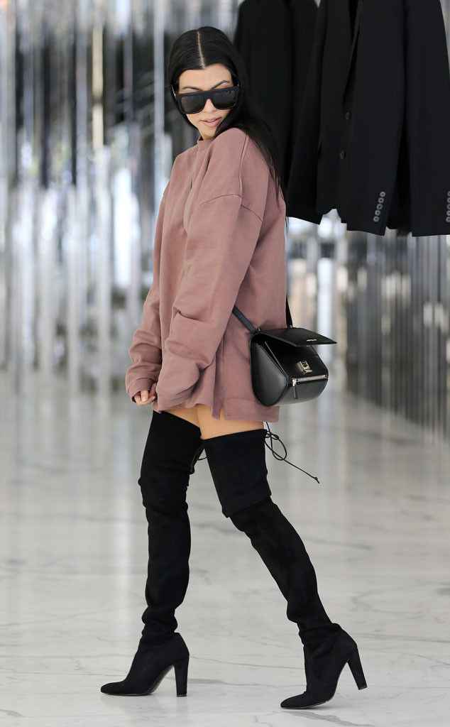 Kourtney Kardashian is killing it with her oversized sweatshirt and boots.