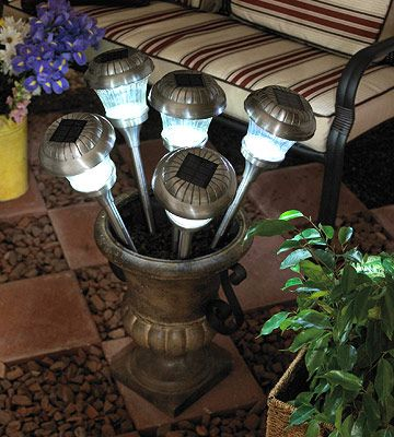 Solar Tiki Torches  For a fun update to traditional tiki torch lighting at your next outdoor party, substitute solar path lights. The gentle illumination lasts for hours. Here they are clustered in a garden urn. You can also place them in individual containers with potted plants for more dispersed effect.