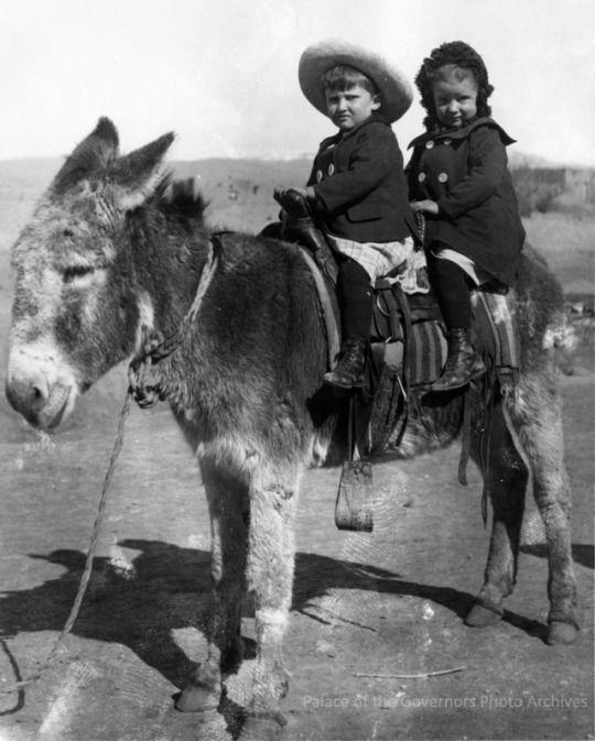 1900, Arthur Bibo and Irma Bibo Floorsheim, children of Emil and Elizabeth Bibo, riding burro in Cubero, New Mexico...Photographer: Emil Bibo