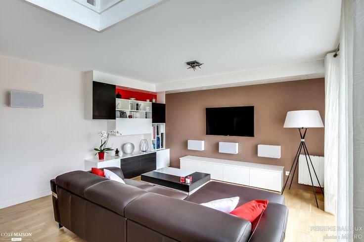 Salon moderne et contemporain. Canapé marron, télévision accrochée au mur.