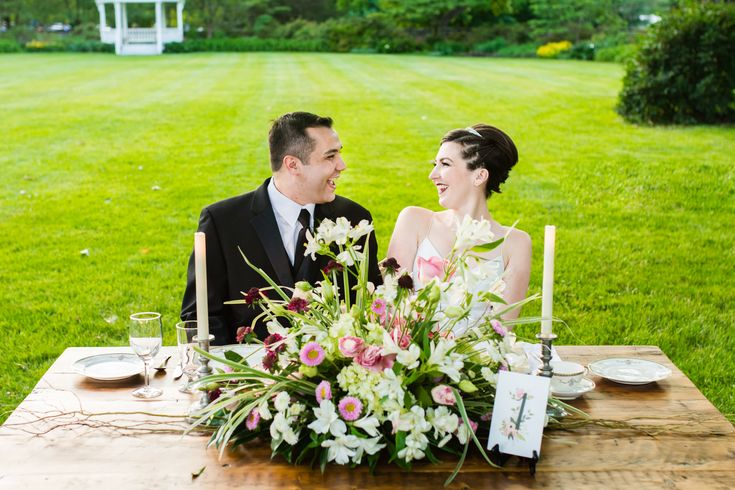 The bride and groom sharing a moment seated at their sweetheart farm table decorated with a centerpiece of blush pink and white wildflowers.