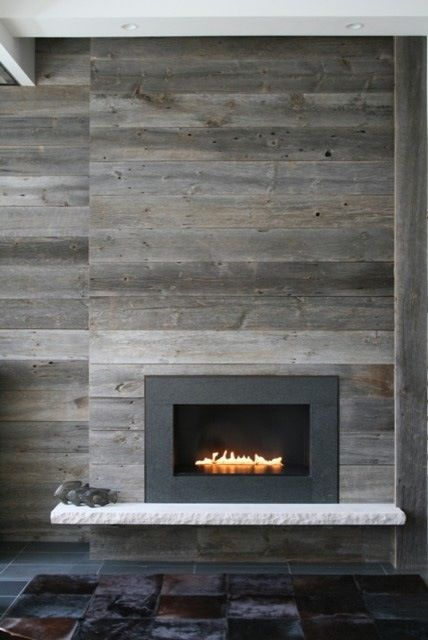 The temps have been seriously dropping around here, and we've got fireplaces on the brain. One trend we've noticing is wood not only inside the fireplace, but on the outside, too. From slick matchbooked panels to reclaimed boards, wood fireplace surrounds are something we're really warming up to.