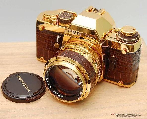 """El 25 de agosto de 1981, Pentax produjo una edición limitada de sus cámaras que llamó """"LX Oro"""". Estaba revestida de de oro enchapado de 18 quilates y cuero de lagarto o de serpiente. Estaba equipado con un f/1.2 Pentax SMC 50mm con lente también revestido en cuero marrón y acabado en dorado."""