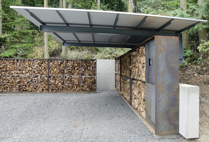 located in a grove of trees, the three-sided, partially-covered structure provides protected parking for a single car, with two additional uncovered spots for guests.