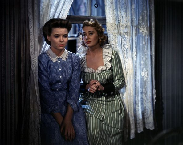Actresses Dorothy McGuire and Joan Blondell are both seated on the sill of the window looking wistfully in vacuum; they play the roles of Katie Nolan, an Irish American worried about the economic hardship of her family, and her wacky sister Sissy, in A Tree Grows in Brooklyn; Katie's concern refers even to the influence of Aunt Sissy, who just got married for the third time, upon her children. Los Angeles, California (USA), 1944 - December 31, 1939