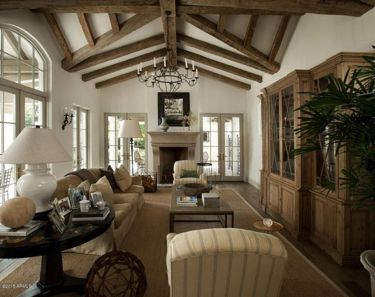 Traditional Living Room with Chandelier, Hardwood floors, Wall sconce, French doors, Exposed beam, metal fireplace
