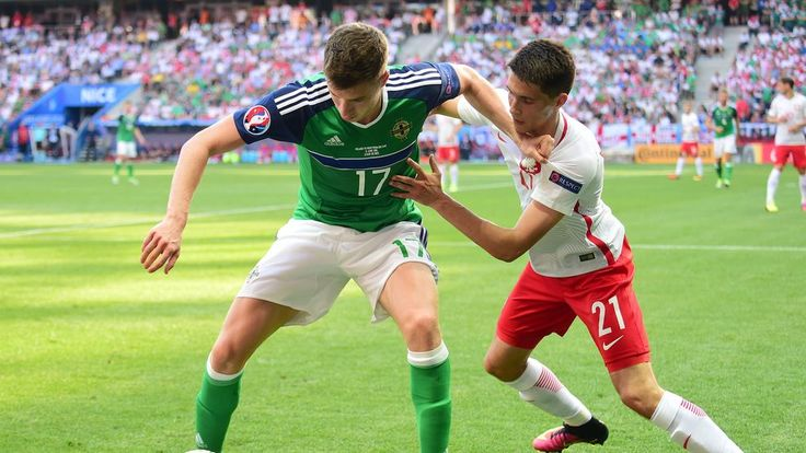 Paddy McNair of Northern Ireland in action with Bartosz Kapustka (R) of Poland during their UEFA EURO 2016 Group C match