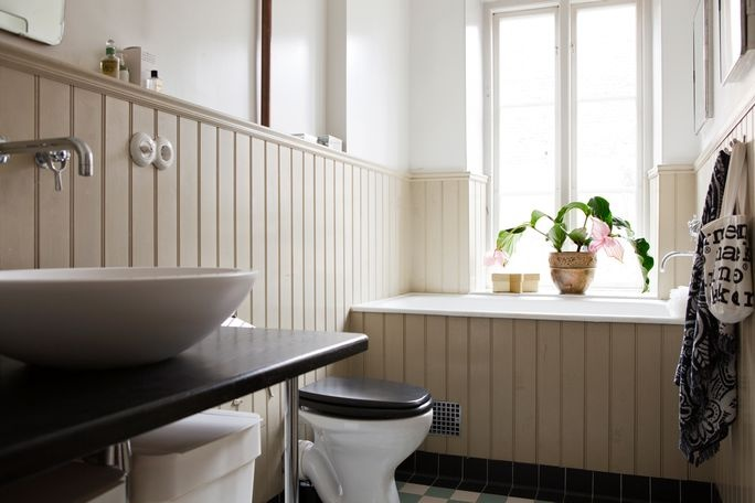Lovely wood paneled bathroom with Victorian floor tiles, porcelain electric sockets and other details from Byggfabriken.