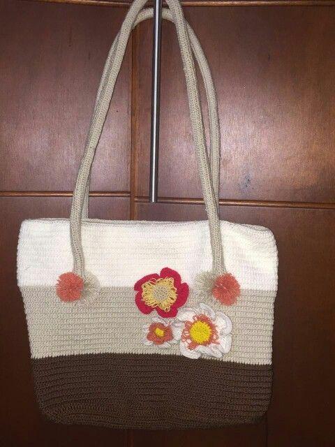 Bolso hecho en crochet, adornado con flores a crochet.