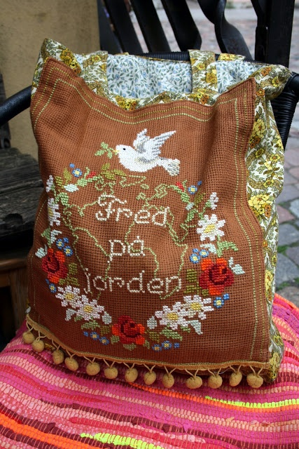Upcycled embroidery tote bag. The text says Peace on earth in Swedish.