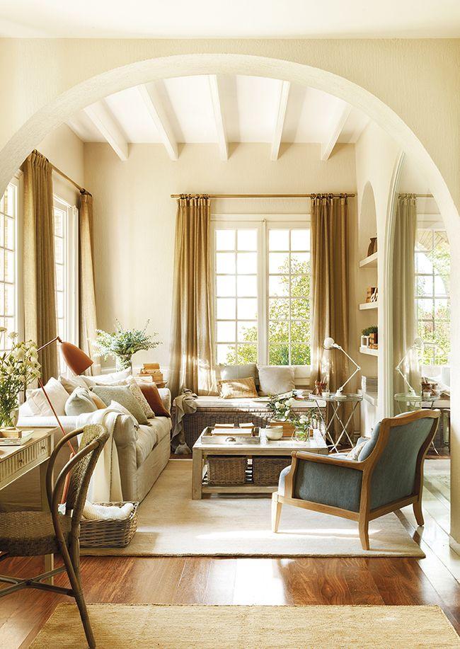 Salón pequeño con ventanas en L, sofá lleno de cojines, butaca, banco bajoventana, paredes tono arena y techo blanco_389567