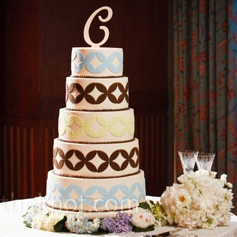 """The five-tiered cake featured the same colorful graphic pattern used on the couple's invitations. A large letter """"C"""" topped off the confection."""