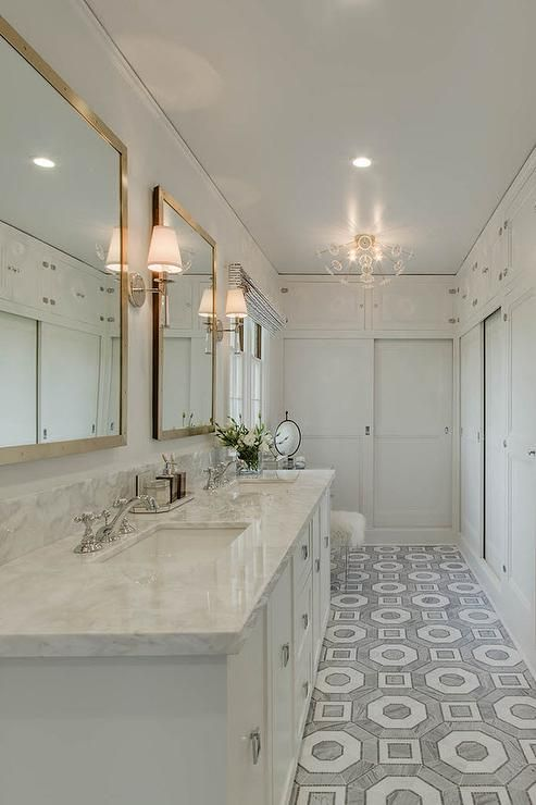 Exquisite long master bathroom with Walker Zanger Villa D'Oro Palermo floor tiles features a long white vanity finished with Rejuvenation Winslow square ring pulls and Calcutta marble countertops and backsplash.